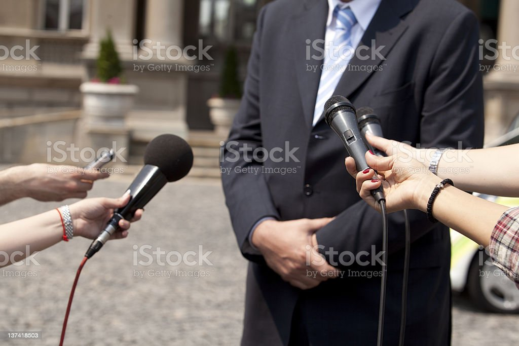 Man surrounded by microphones during an interview royalty-free stock photo