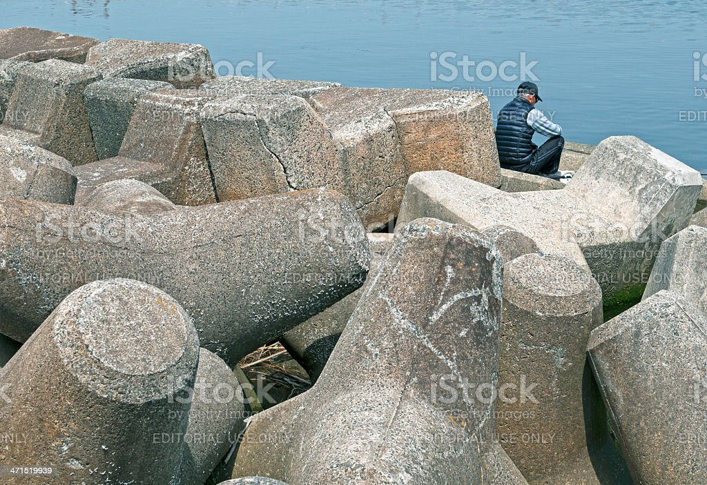 Man surrounded by tetrapods fishing in river royalty-free stock photo