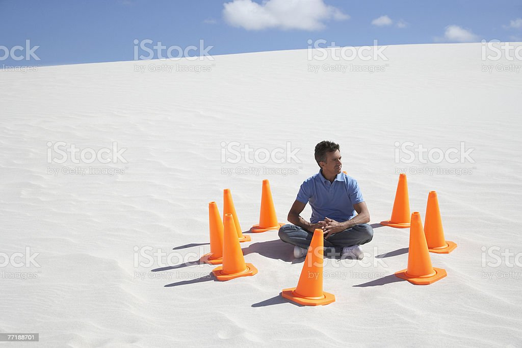 A man surrounded by traffic cones in the middle of nowhere royalty-free stock photo