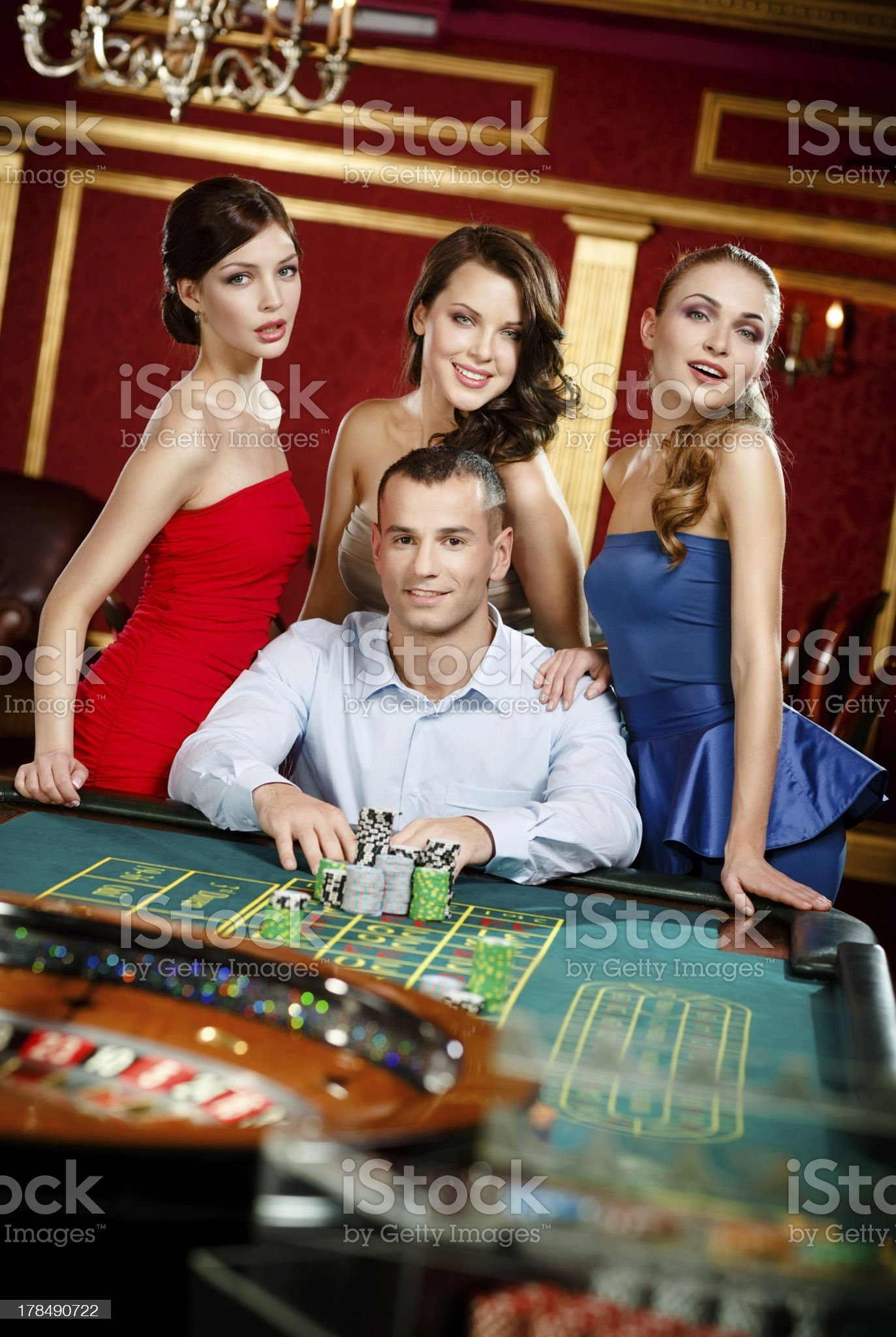 Man surrounded by young girls gambles roulette royalty-free stock photo