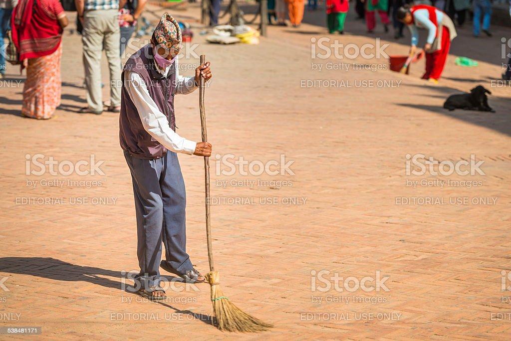 Man sweeping with broom in Patan Durbar Square Kathmandu Nepal stock photo