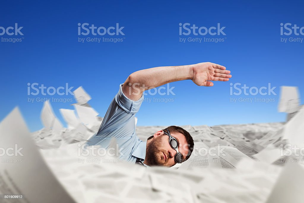 Man swimming in papers stock photo