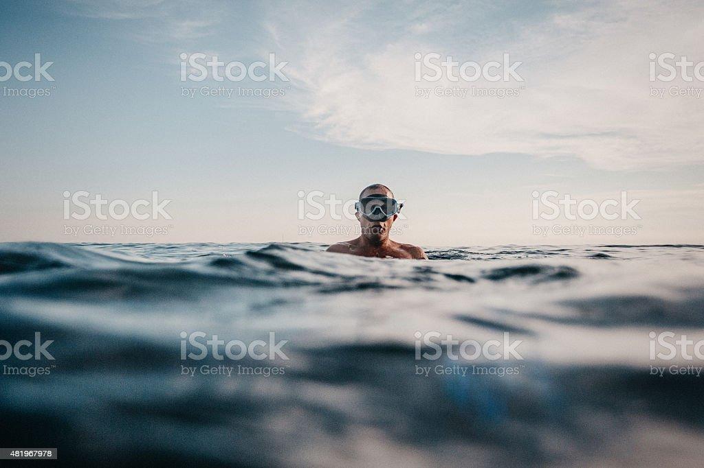 Man swimming in sea with scuba mask stock photo