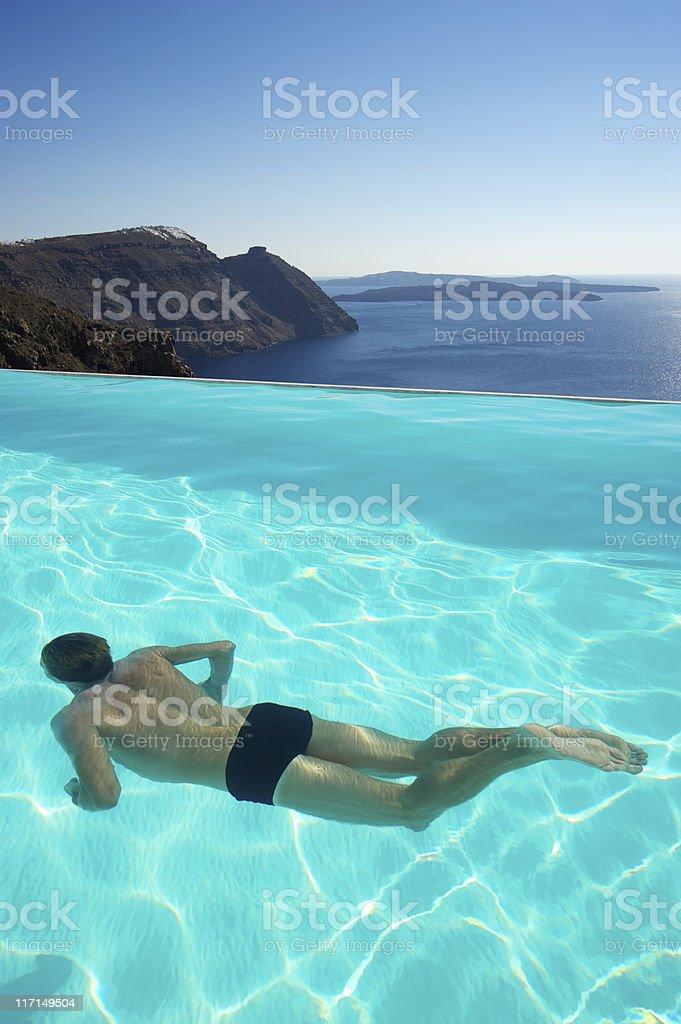 Man Swimming Underwater in Infinity Pool royalty-free stock photo
