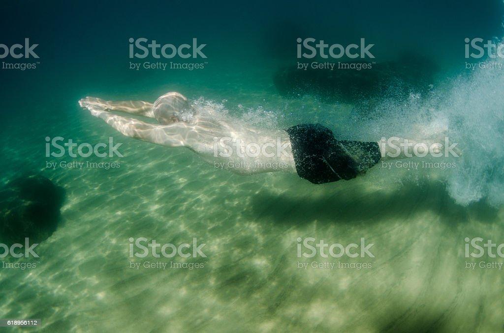 Man swimming underwater in Lake Tahoe stock photo