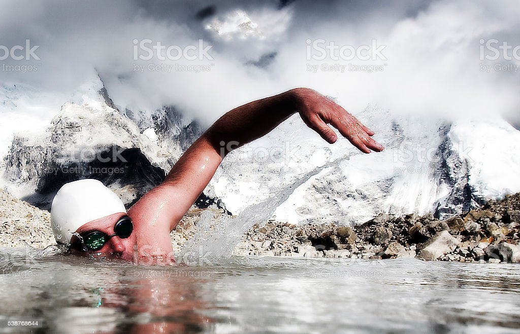 Man swims in icy water with swimming  goggles and cap stock photo
