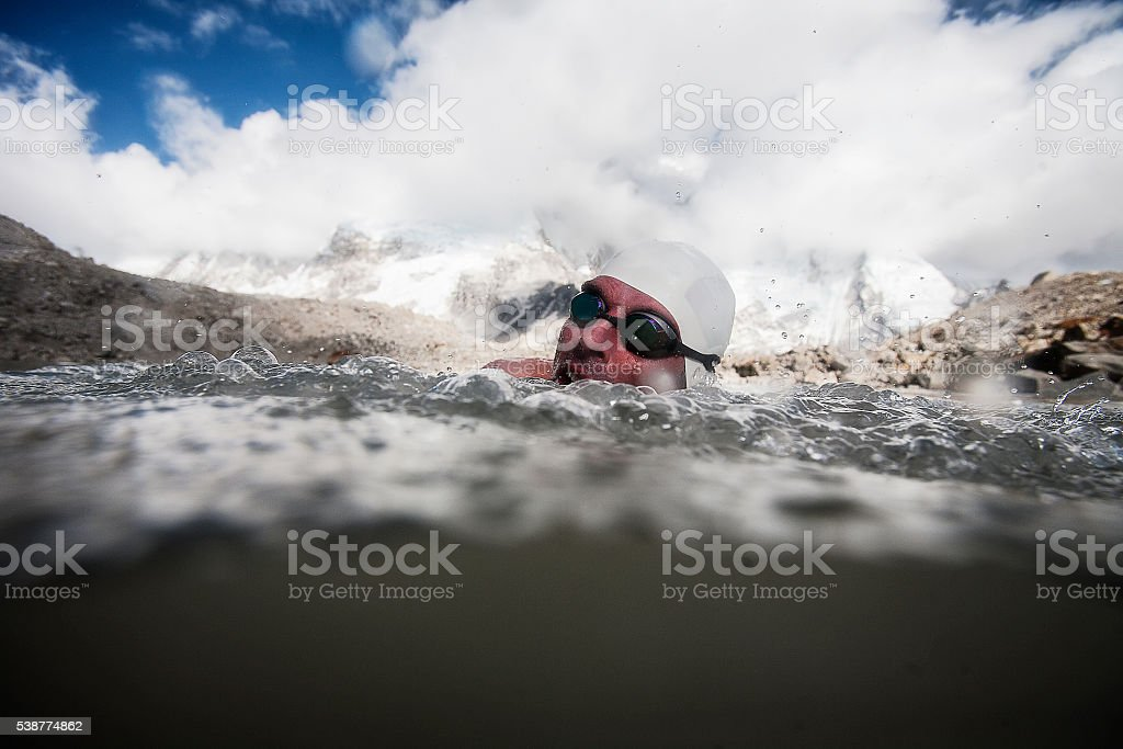 Man swims in freezing water with swimming goggles and cap stock photo