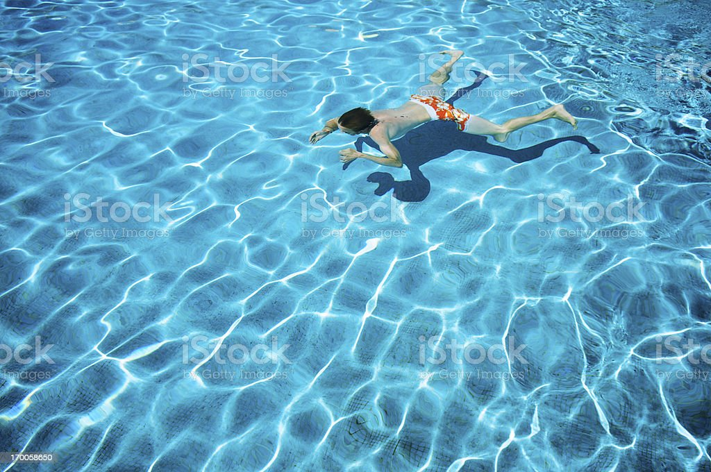 Man Swims Underwater in Bright Swimming Pool royalty-free stock photo