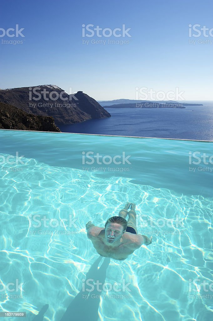 Man Swims Underwater in Infinity Pool w Dramatic View royalty-free stock photo
