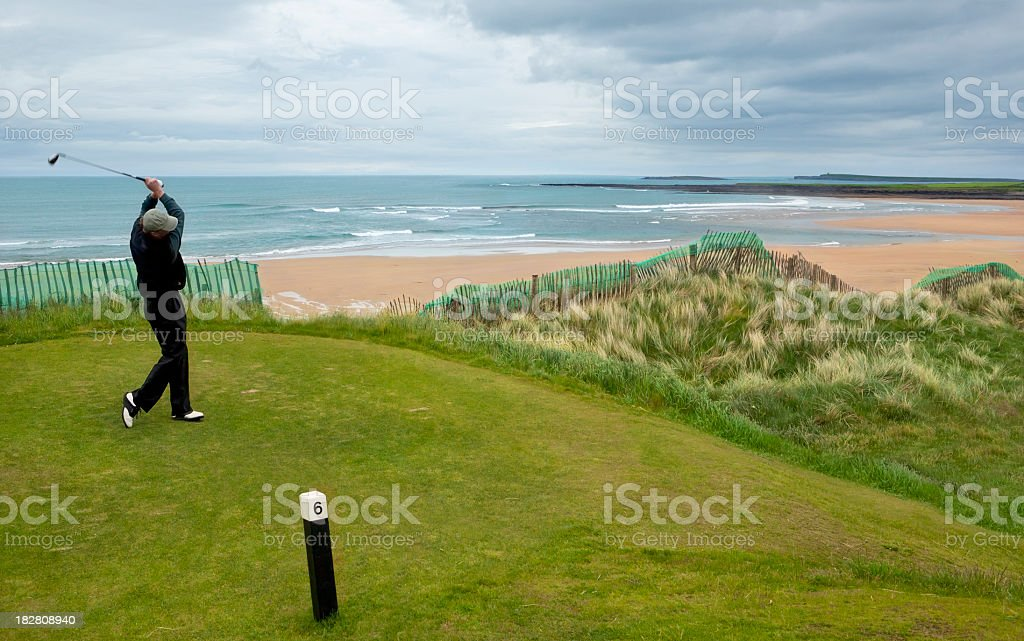 Man swinging club while golfing by the ocean in Ireland royalty-free stock photo