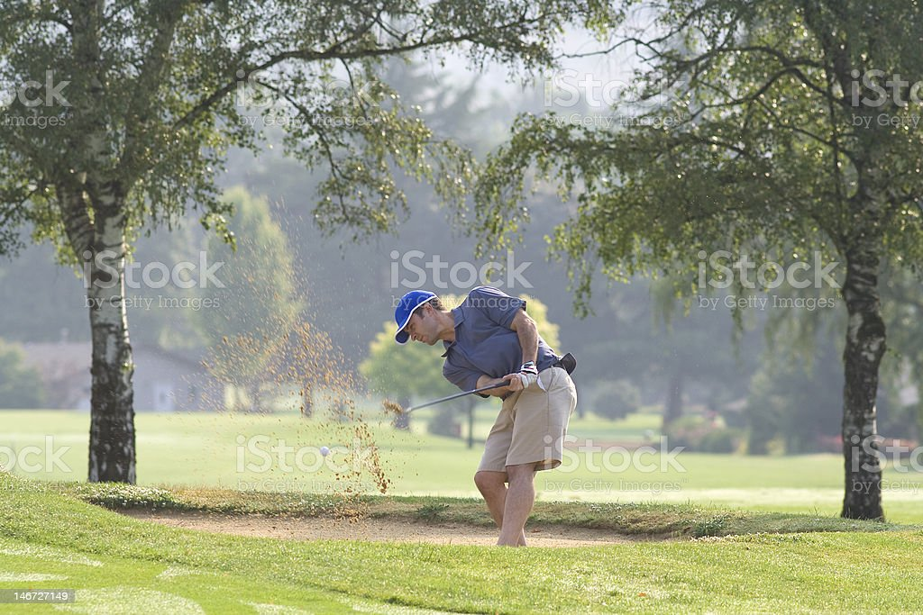 Man swinging from sand trap - Horizontal royalty-free stock photo