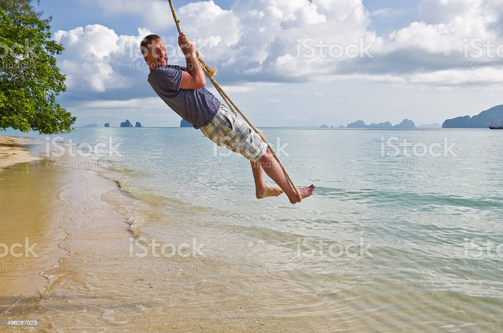 Man swings out over paradise beach in Thailand stock photo