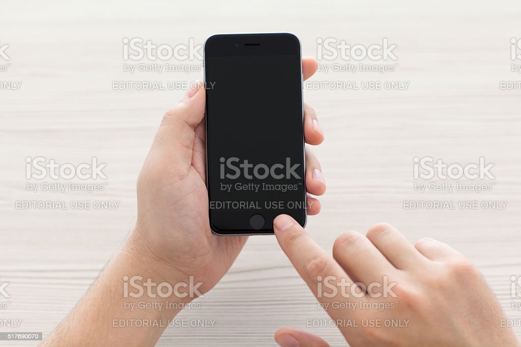 Man switch on the new iPhone 6 Space Gray holding stock photo