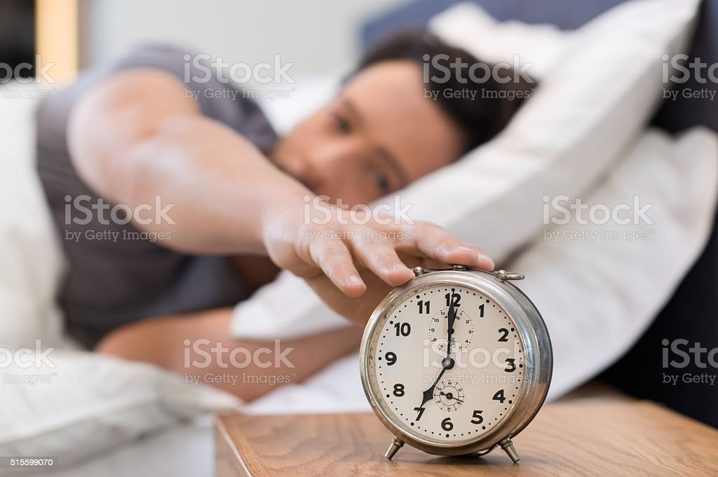 Man switching off alarm stock photo