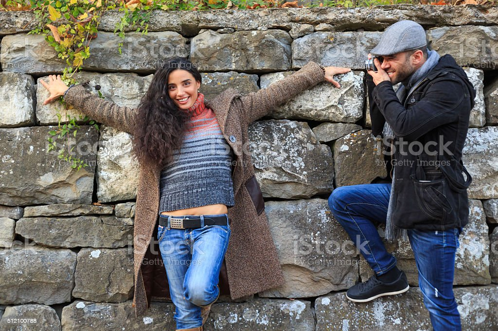 Man take photo of woman in front a stone wall stock photo
