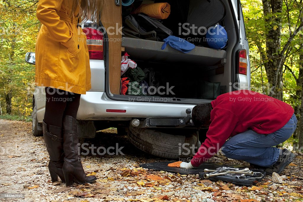 Man taken spare tire woman is waiting stock photo