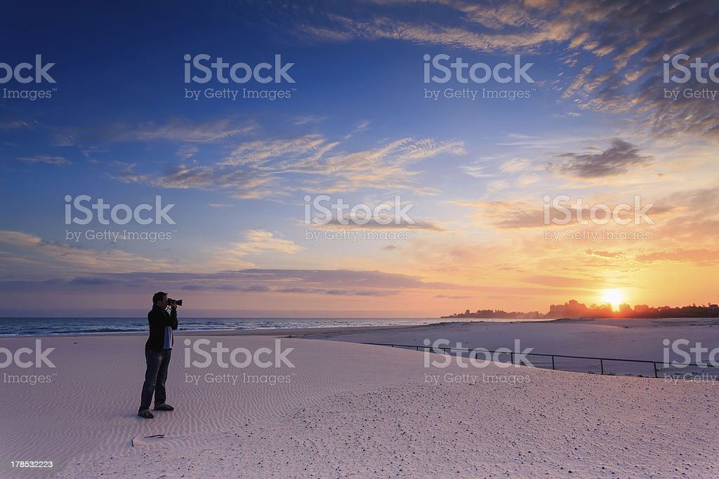 man takes a photograph of sunrise royalty-free stock photo