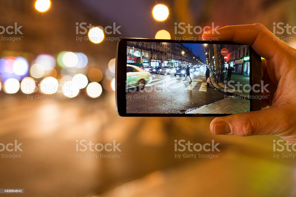 Man takes a picture in the street with mobile phone. stock photo