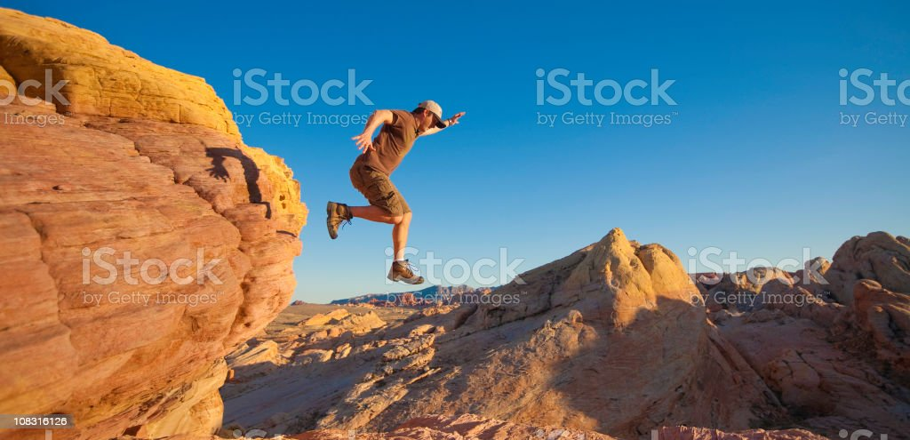 Man takes leap of faith off of rock outcropping royalty-free stock photo