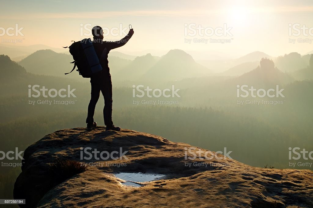 Man takes photos with smartphone in morning misty  mountains stock photo