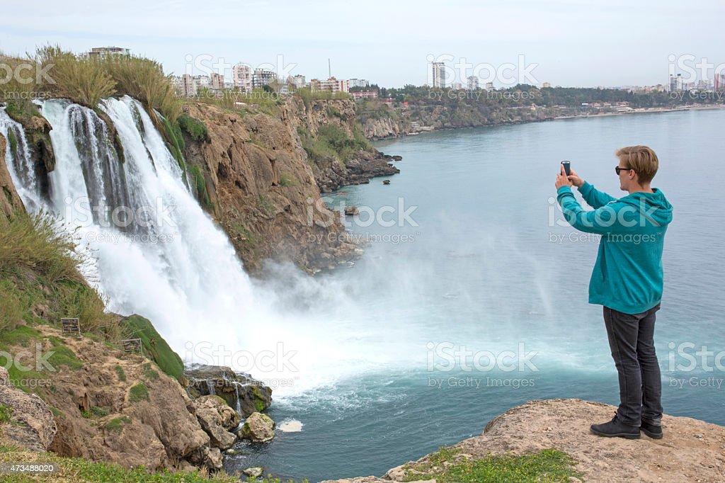 Man takes picture of urban waterfall, sea below stock photo