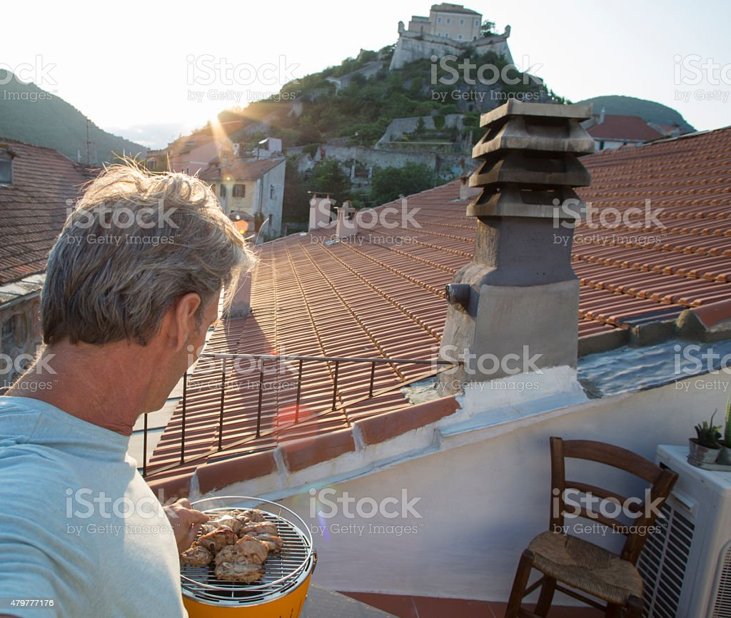 Man takes selfie barbecuing on a rooftop in Liguria, Italy. stock photo
