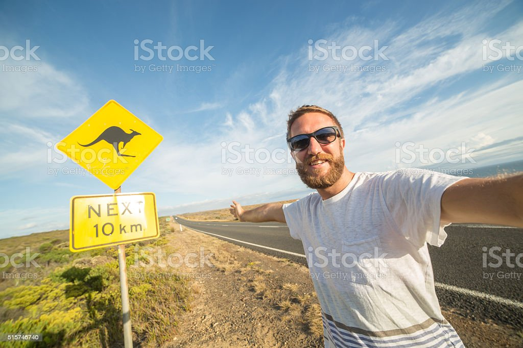 Man takes selfie portrait with warning road sign in Australia stock photo