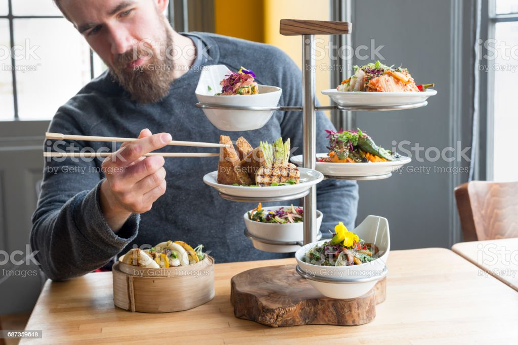 Man Takes Tofu Using Chopsticks from Tiered Server in Restaurant stock photo