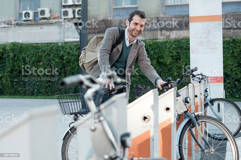 man taking a bike in a bike sharing city service stock photo