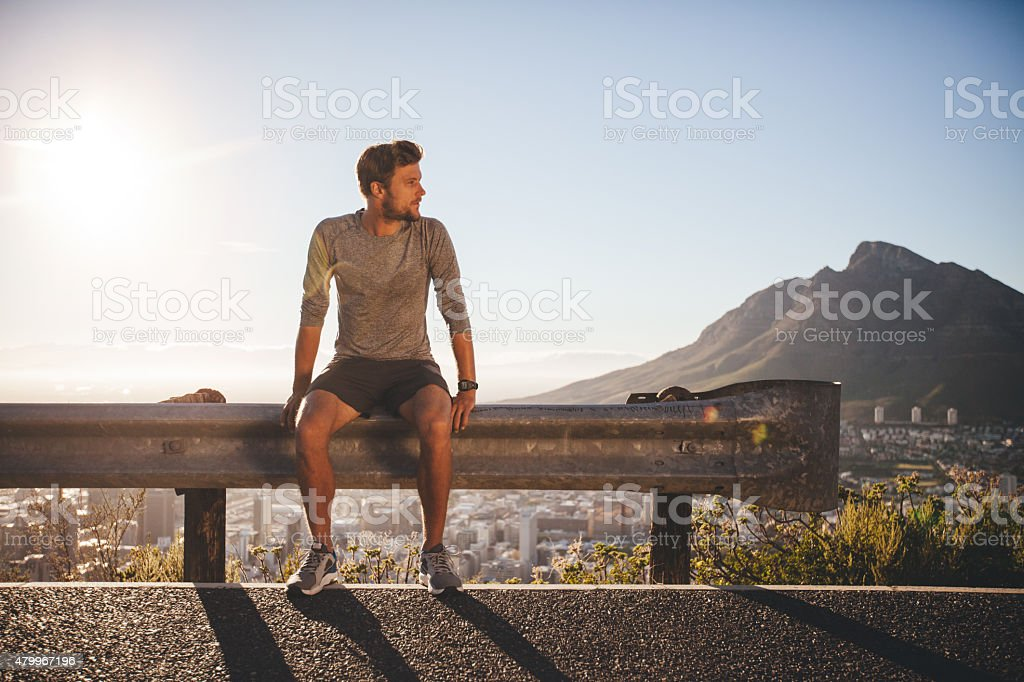 Man taking a break after morning run stock photo