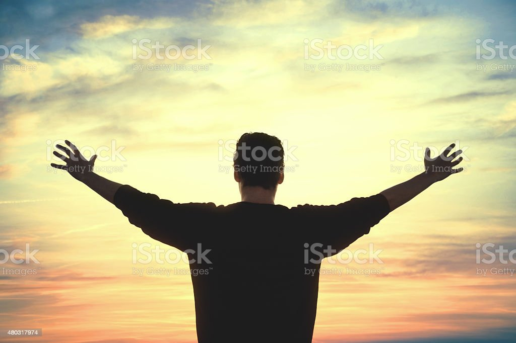 Man taking a deep breath at sunset stock photo