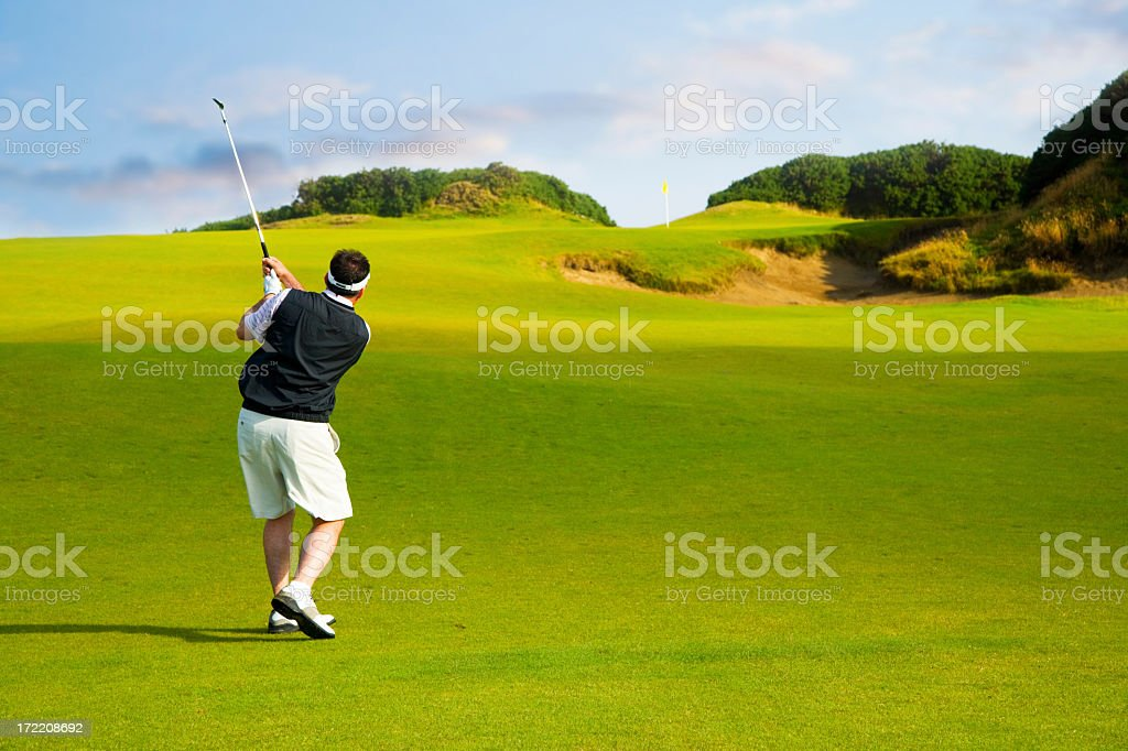 Man taking a golf shot from the middle of the fairway  royalty-free stock photo