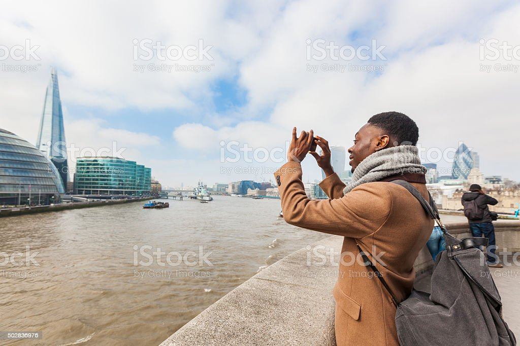 Man taking a picture in London with his smart phone stock photo