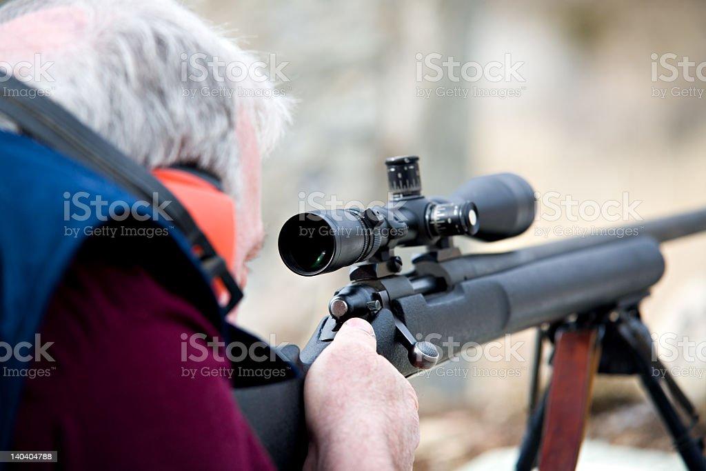 A man taking aim through the scope of a rifle stock photo