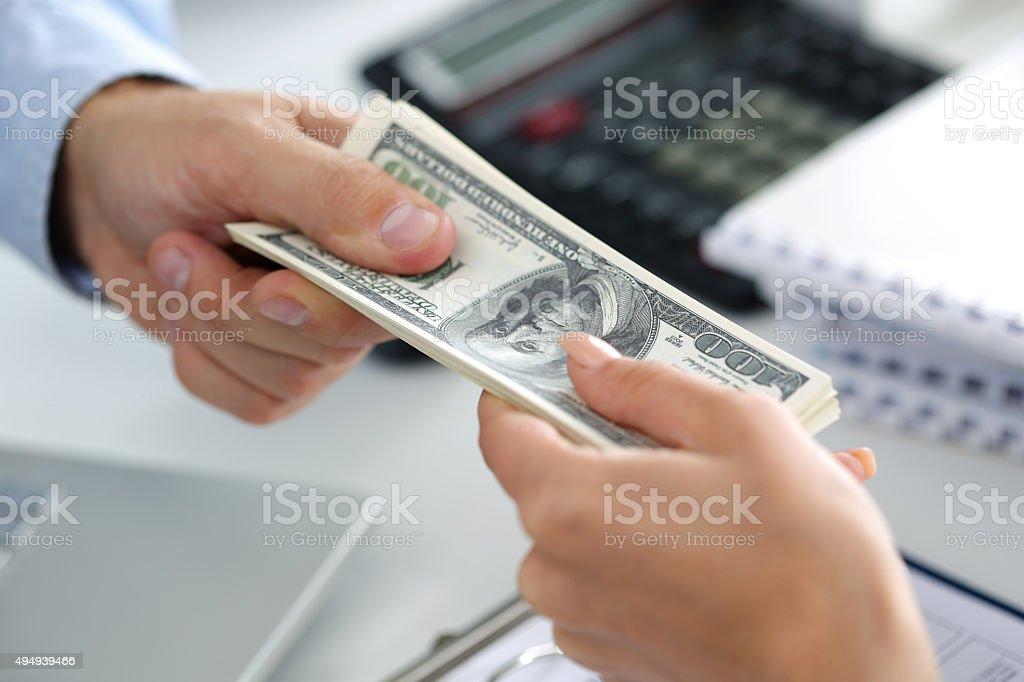 Man taking batch of hundred dollar bills stock photo