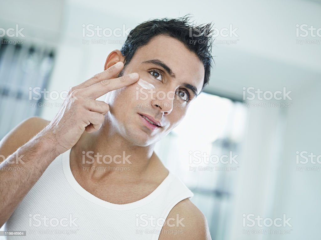 Man taking care of his skin with cosmetic products royalty-free stock photo