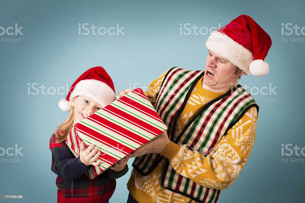 Man Taking Christmas Gift Away From Little Girl royalty-free stock photo