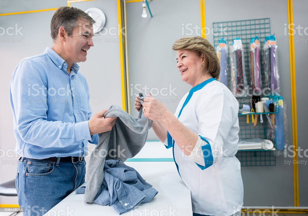 Man taking clothes to the laundry shop stock photo