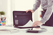 Man taking documents from briefcase, close up of hands