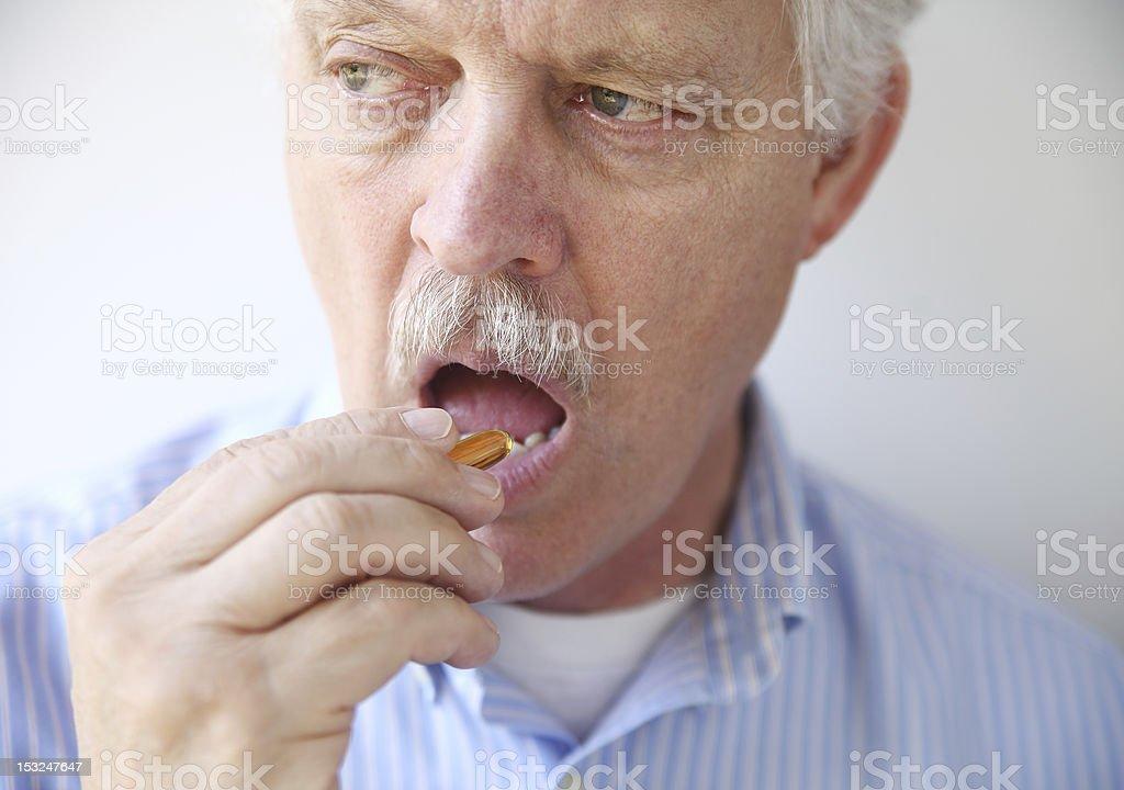 man taking fish oil pill royalty-free stock photo