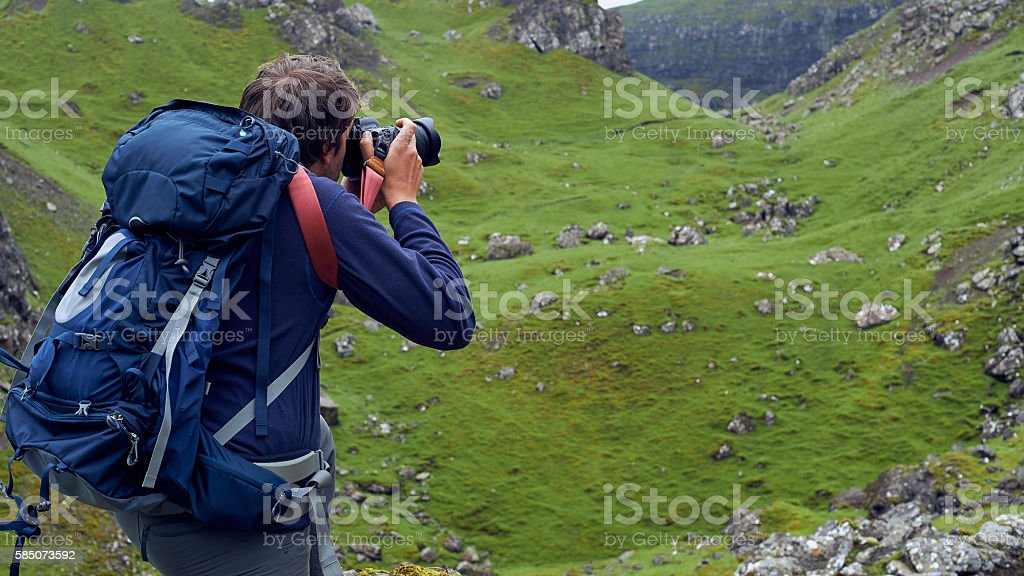 Man taking images of the beautiful scottish landscape stock photo