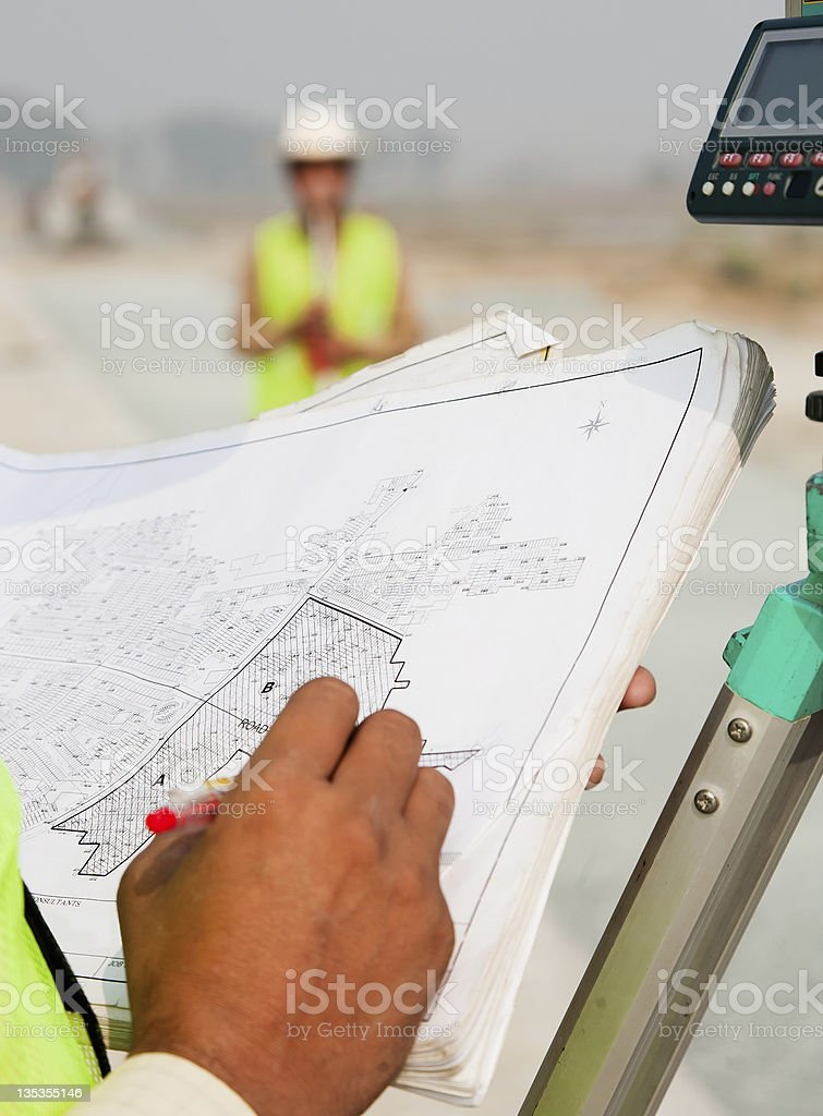 man taking measurements on theodolite stock photo