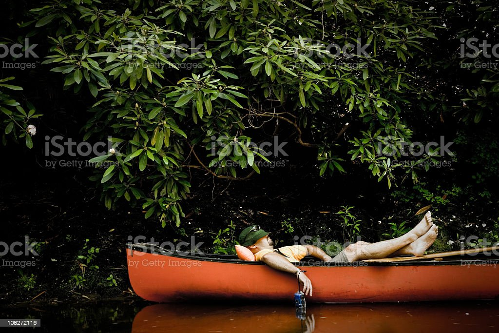 Man Taking Nap in Canoe royalty-free stock photo