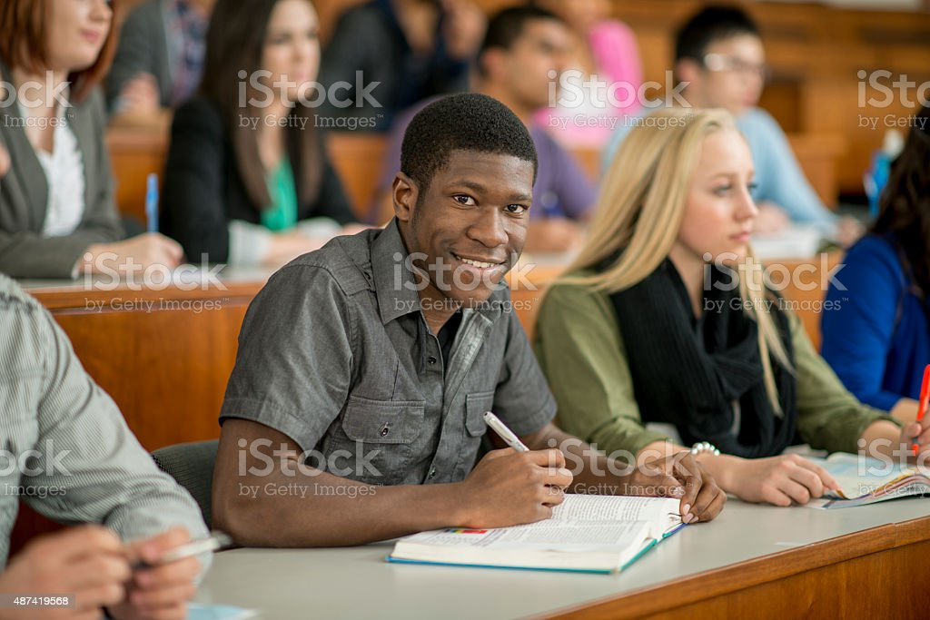 Man Taking Notes in Class stock photo