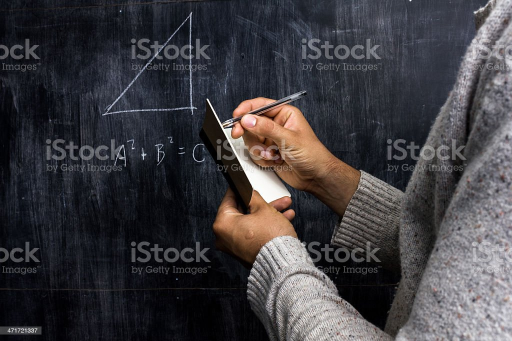 Man taking notes of math theorem on blackboard stock photo