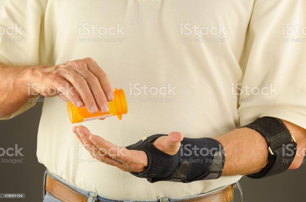 Man taking pain anti-inflammatory tendinitis medication stock photo