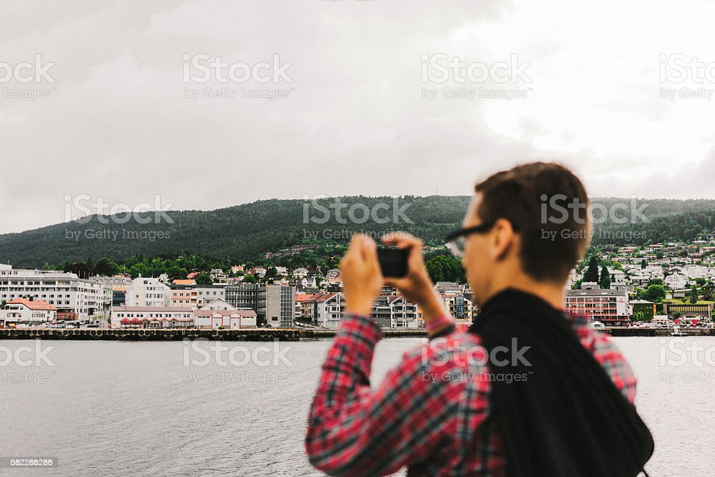 Man taking photo of city on smartphone stock photo