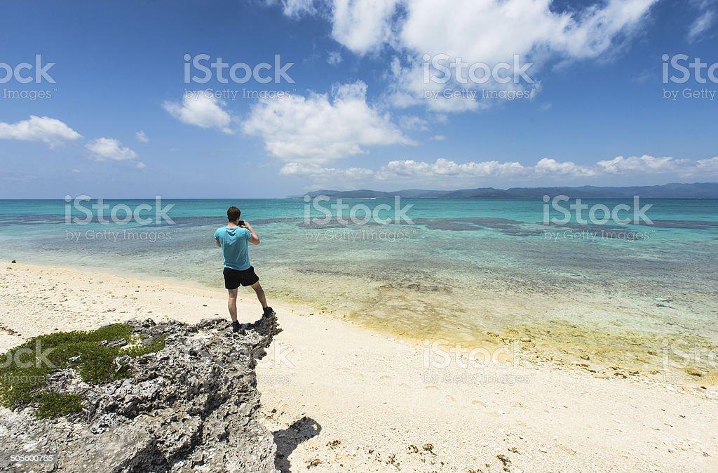 Mann nehmen Foto von idyllischen tropischen coral beach Lizenzfreies stock-foto