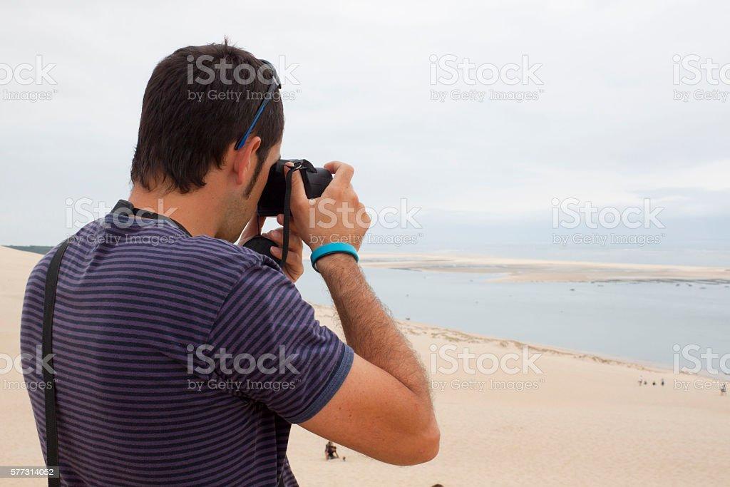 Man taking photos of the sea and the coast stock photo