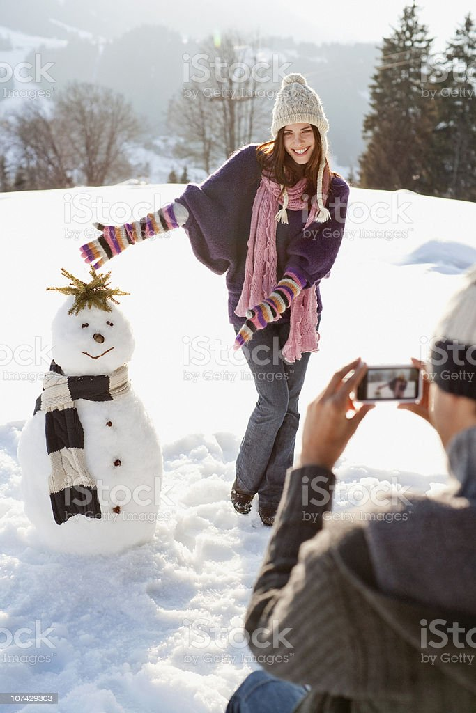 Man taking picture of girlfriend and snowman royalty-free stock photo